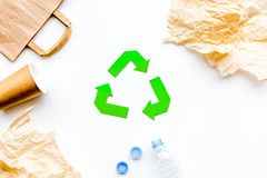 Sorting waste and recycle. Green paper recycling sign on white background top view space for text. Sorting waste and recycle. Green paper recycling sign on white Stock Images