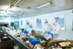 Sorting on Waste Recycling Plant. Portrait of two workers wearing biohazard suits working at waste processing plant sorting trash on conveyor belt, copy space stock image