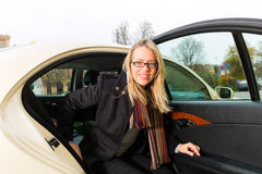 Sortir de jeune femme du taxi Photo stock