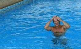 Sortir de sourire d'homme du wate bleu de piscine Image libre de droits