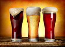 Sorts of beer. Three glasses of beer on a wooden table Stock Photos