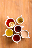 Sorts of tea in the cups. Over wooden table Royalty Free Stock Images