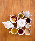 Sorts of tea in the cups and tea pots. Over wooden table Stock Image
