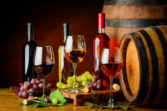 Sorts of wine in bottles and glasses. Pinot gris, Cabernet sauvignon and pinot noir in cellar with barrels royalty free stock images