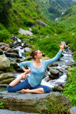 Sorty fit woman doing yoga asana outdoors at tropical waterfall. Hatha yoga outdoors - young sporty fit woman doing yoga asana Eka pada rajakapotasana - one stock photo