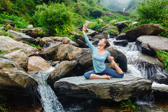 Sorty fit woman doing yoga asana outdoors at tropical waterfall. Hatha yoga outdoors - young sporty fit woman doing yoga asana Eka pada rajakapotasana - one royalty free stock images