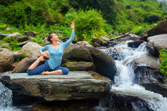 Sorty fit woman doing yoga asana outdoors at tropical waterfall. Hatha yoga outdoors - young sporty fit woman doing yoga asana Eka pada rajakapotasana - one royalty free stock photos