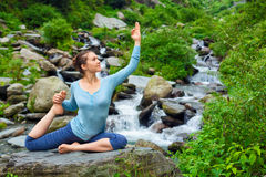 Sorty fit woman doing yoga asana outdoors at tropical waterfall. Hatha yoga outdoors - young sporty fit woman doing yoga asana Eka pada rajakapotasana - one Royalty Free Stock Image