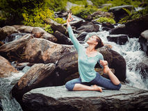 Sorty fit woman doing yoga asana outdoors at tropical waterfall. Vintage retro effect hipster style image of sporty fit woman doing yoga asana Eka pada Stock Images