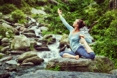 Sorty fit woman doing yoga asana outdoors at tropical waterfall. Vintage retro effect hipster style image of sporty fit woman doing yoga asana Eka pada stock photos