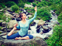 Sorty fit woman doing yoga asana outdoors at tropical waterfall. Young sporty fit woman doing yoga asana Eka pada rajakapotasana - one-legged king pigeon pose at Stock Photography