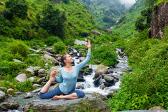 Sorty fit woman doing yoga asana outdoors at tropical waterfall. Yoga outdoors - young sporty fit woman doing stretching yoga asana Eka pada rajakapotasana - one royalty free stock photos