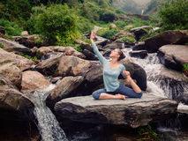 Sorty fit woman doing yoga asana outdoors at tropical waterfall. Yoga outdoors - young sporty fit woman doing stretching yoga asana Eka pada rajakapotasana - one royalty free stock image