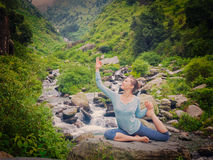 Sorty fit woman doing yoga asana outdoors at tropical waterfall. Yoga outdoors - young sporty fit woman doing stretching yoga asana Eka pada rajakapotasana - one royalty free stock photo