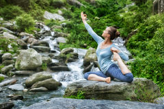 Sorty fit woman doing yoga asana outdoors. Young sporty fit woman doing yoga asana Eka pada rajakapotasana - one-legged king pigeon pose at tropical waterfall Stock Photo
