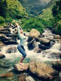 Sorty fit woman doing yoga asana Utkatasana outdoors Royalty Free Stock Photo