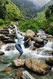 Sorty fit woman doing yoga asana Utkatasana. Young sporty fit woman doing yoga asana Utkatasana (chair pose) outdoors at tropical waterfall standing on stone Stock Image