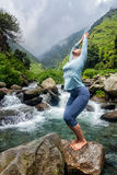 Sorty fit woman doing yoga asana at waterfall. Young sporty fit woman doing yoga asana Utkatasana (chair pose) outdoors at tropical waterfall standing on stone Royalty Free Stock Photo