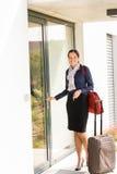 Sorvegliante di volo sorridente di affari della donna che arriva a casa Fotografia Stock