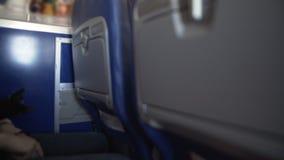 Sorveglianti di volo che serviscono i pasti di linea aerea ai passeggeri a bordo dell'aereo di linea video d archivio