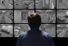Sorveglianza di conduzione della guardia giurata guardando parecchia secur Immagini Stock Libere da Diritti