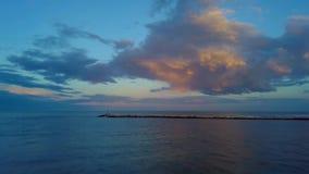 Sorvolamento sul mare al tramonto con una diga nella parte anteriore ed in un bello cielo video d archivio