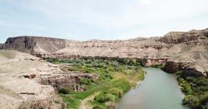 Sorvolare il fiume blu Fiume ampio Sulla riva di erba verde, delle colline, delle montagne e della steppa stock footage