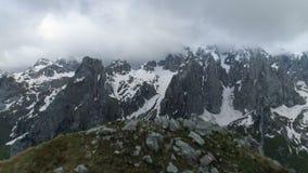 Sorvolare la cima della montagna verso le più alte e montagne nevose, aerea stock footage
