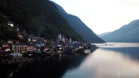 Sorvolare la città famosa Hallstatt nelle alpi austriache Le vecchie case e chiese tradizionali ad alba stock footage