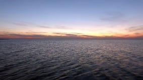 Sorvolare la superficie dell'acqua al tramonto stock footage