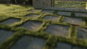 Sorvolare pavimenta le pietre in un prato inglese con abbagliare di Sun stock footage