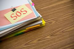 SOS  Ο σωρός των επιχειρησιακών εγγράφων σχετικά με το γραφείο Στοκ φωτογραφίες με δικαίωμα ελεύθερης χρήσης
