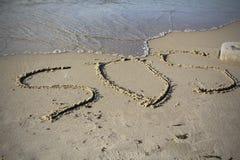 SOS -在与软的波浪的沙子海滩得出的词 免版税库存图片
