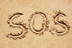 SOS. S.O.S written in the sand with a finger or stick stock photo