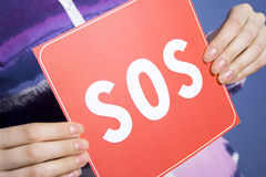 SOS. The hands of a young girl holding a card from the paper with the inscription of the SOS. Located in the premises stock images