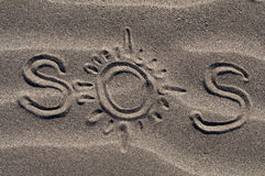SOS. S.O.S written in the sand with a finger or stick stock photos