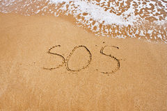 SOS. Drawn on the sand in a summer day Stock Images