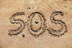 SOS. Message on the coast, written in the sand stock photos