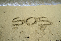 Sos. Writting in the sand on beach. Message saying sos a cry for help Stock Photography