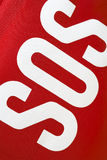 SOS. (save our souls) lettering on a red fabric first aid kit Royalty Free Stock Photo
