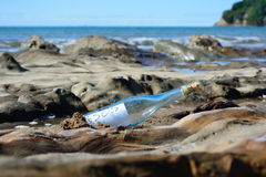 SOS bottle. A glass bottle with an SOS message on the coast Royalty Free Stock Image