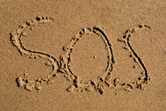 SOS. Casual writing in the wet sand on a sunny day Stock Photos