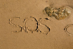SOS. Casual writing in the wet sand on a sunny day Royalty Free Stock Images