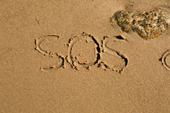 SOS. Casual writing in the wet sand on a sunny day royalty free stock photo