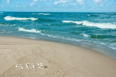 SOS on the coast. Ssandy beach with a word SOS written with seashells Royalty Free Stock Image