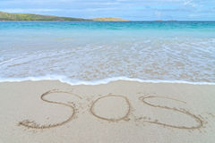 SOS distress sign. Written in sand of tropical island beach above water royalty free stock photos