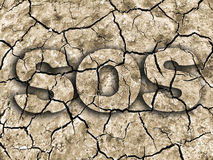 SOS drought. Dry cracked earth texture from dry lake with sign SOS. Photo-montage Stock Photo
