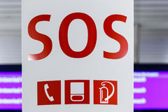 SOS emergency sign. For a telephone, fire extinguisher and assistance with bold red lettering over white stock photos
