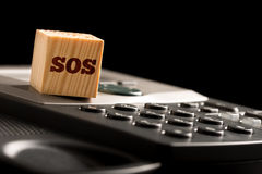 SOS emergency telephone communication. Concept with a wooden block with the letters SOS resting on the keypad of a landline telephone , low angle closeup with Royalty Free Stock Image