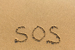 SOS - escrito manualmente na textura da areia do mar ajuda Fotografia de Stock Royalty Free